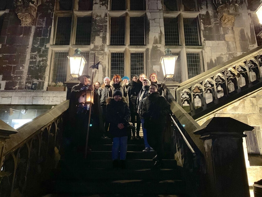 A group of people on the stairs of Aachen City Hall at night-time